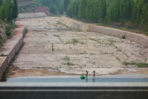 Two guys and a boy washing themselves at a dam