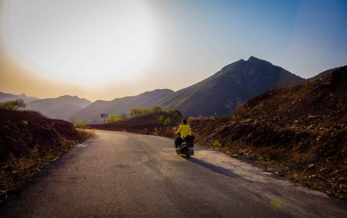 Women riding her motorbike through backroads of CHina